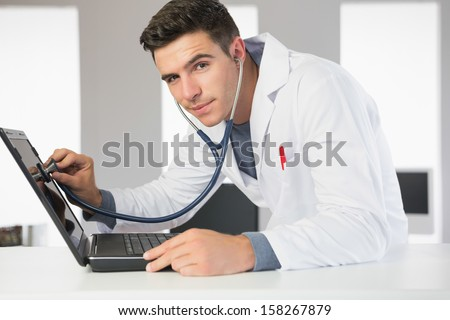 Attractive smiling computer engineer examining laptop with stethoscope in bright office