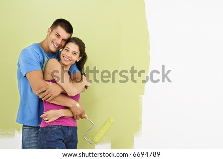 Attractive smiling couple posing in front of partially painted wall holding paint roller. - stock photo