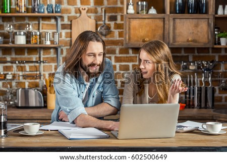 Attractive smiling couple talking and gesturing while using laptop at home