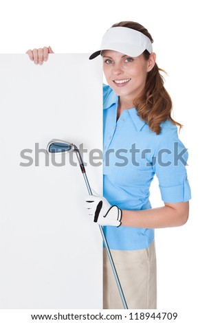 Attractive smiling female golfer holding a golfclub and a large blank board with copy-space for your advertising and marketing