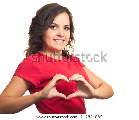 Attractive smiling girl in a red shirt makes the sign of the heart with her fingers. Isolated on white background
