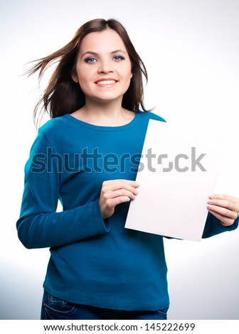 Attractive smiling girl in blue shirt holding a poster,on white background.