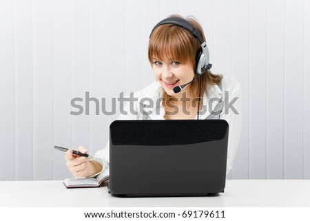 attractive smiling girl in headphones with a microphone works with a laptop and notebook - stock photo