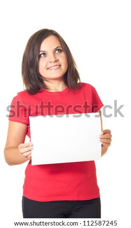 Attractive smiling girl in red shirt holding a poster and looks to the upper-left corner. Isolated on white background