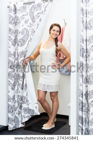 Attractive smiling girl trying on new dress at apparel store