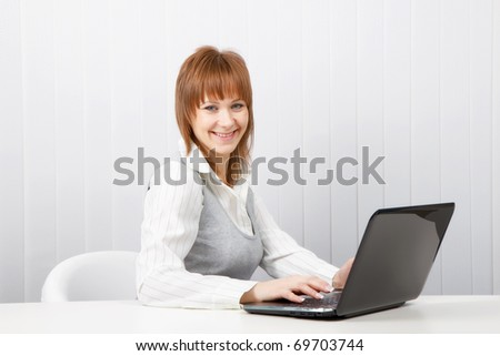 Attractive smiling happy girl with a laptop in the office - stock photo