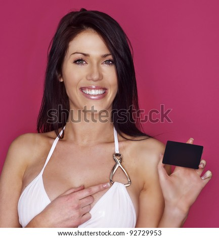 Attractive smiling happy woman pointing to black card that she is holding - stock photo