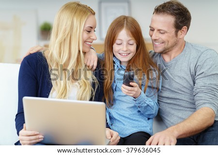 Attractive smiling happy young girl checking her mobile for messages as she sits on the couch at home relaxing with her parents