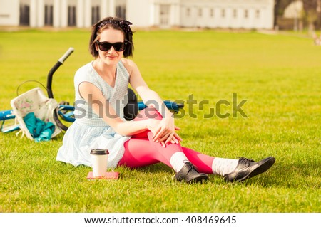 Attractive smiling hipster woman in casual clothes standing on grass near her vintage bicycle with a book and a cup of coffee - stock photo