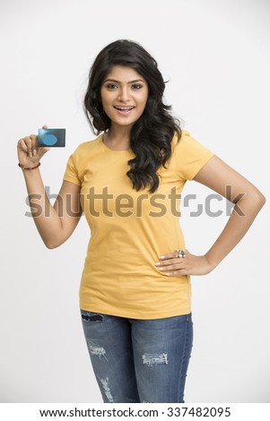 Attractive smiling Indian young girl with credit card on white. - stock photo