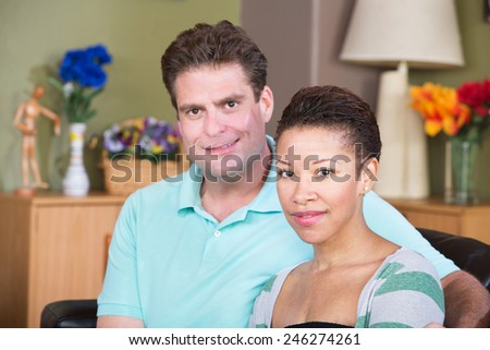 Attractive smiling male and female couple sitting together - stock photo