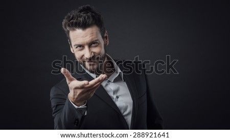 Attractive smiling man showing or welcoming somebody with open hand - stock photo