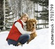 Attractive smiling mid adult Caucasian blond woman squatting in snow with arms around Golden Retriever. - stock photo