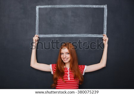 Attractive smiling redhead young woman holding a frame drawn on blackboard background above her head  - stock photo