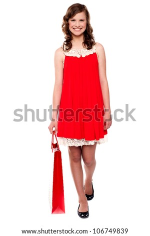 Attractive smiling teenager walking with shopping bag - stock photo