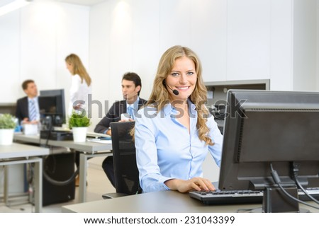 Attractive smiling woman at her desk with handset with people working at the background - stock photo
