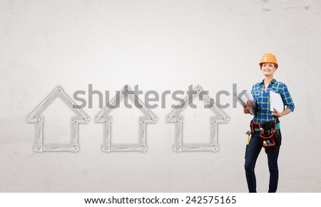 Attractive smiling woman engineer wearing helmet and tool belt