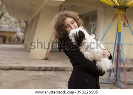 Attractive smiling woman holding dog  in the park