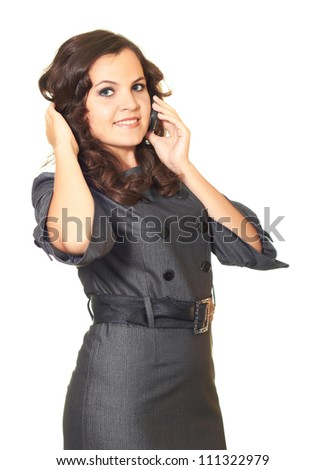 Attractive smiling woman in a business dress and long brown curly hair talking on the phone. Isolated on white background