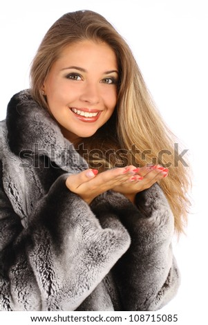Attractive smiling woman in a gray coat with open hands palm for product - stock photo
