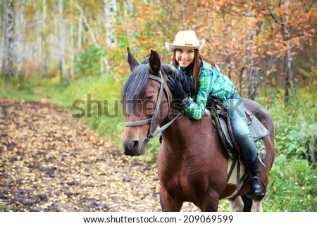 Attractive smiling woman in a hat riding a horse - stock photo