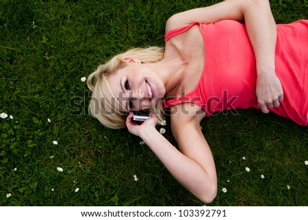 Attractive smiling woman lying on green lawn and talking on her mobile phone - stock photo