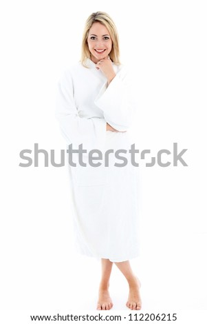 Attractive smiling woman standing barefoot in a white bath robe isolated on a white background - stock photo
