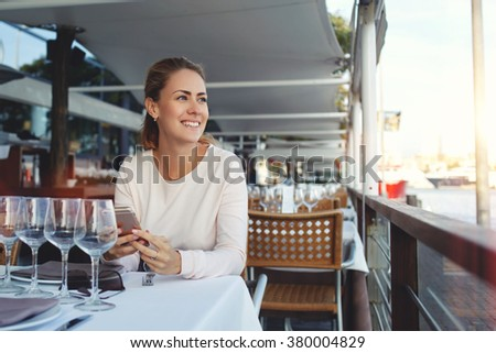 Attractive smiling woman waiting an answer in text messaging from someone while sitting in modern sidewalk cafe, happy female with cell telephone in hands enjoying view during lunch in cozy restaurant - stock photo