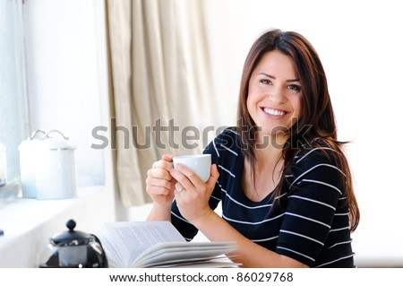 Attractive smiling woman with her cup of tea - stock photo