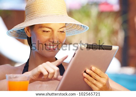 Attractive smiling woman with straw hat using tablet computer in pool - stock photo