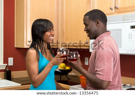 Attractive smiling young African American couple looking at each other standing in a kitchen clinking wine glasses, in a toast.  Horizontally framed shot with the womans face towards the camera.