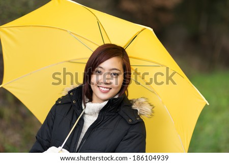 Attractive smiling young Asian woman sheltering under a yellow umbrella as she takes a walk outdoors on an inclement day - stock photo