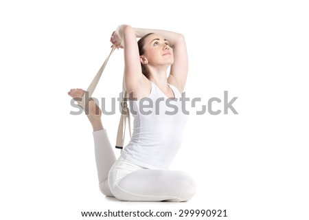 Attractive smiling young beginning yoga student in white sportswear sitting in variation of One-Legged King Pigeon Pose helping herself with strap, studio full length three-quarters view, isolated - stock photo