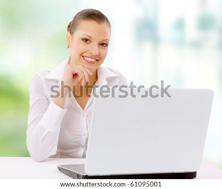 Attractive smiling young business woman using laptop at work desk - stock photo