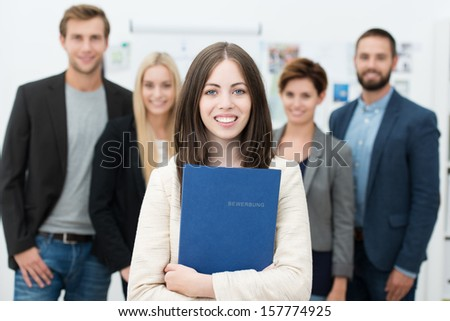 Attractive smiling young businesswoman holding her curriculum vitae in a blue folder as she stands waiting for a job interview with other diverse applicants in the background - stock photo