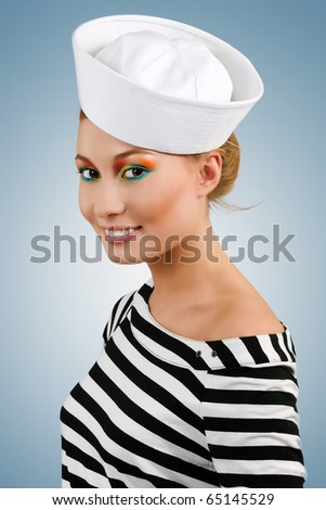 Attractive smiling young girl in sailor's cap - stock photo