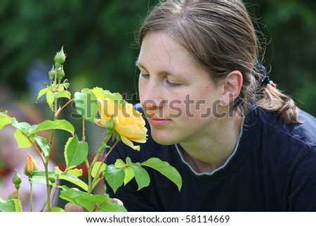 Attractive smiling young lady enjoys her garden