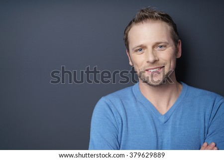 Attractive smiling young man in blue shirt with stubble on face in front of dark background - stock photo