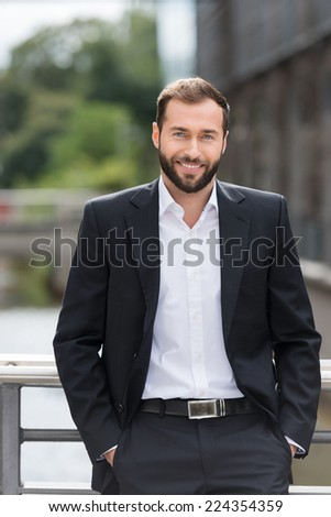Attractive Smiling Young Man in Corporate Attire Outside the Building. Looking at Camera. - stock photo