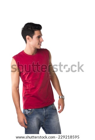 Attractive smiling young man in red sleeveless shirt and jeans, looking to a side at blank space next to him, isolated on white - stock photo