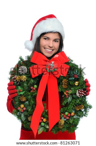 Attractive smiling young woman holding a Christmas Wreath in front of her body. Vertical format over a white background.