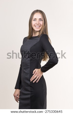 Attractive smiling young woman in a black dress - stock photo