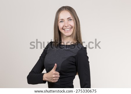 Attractive smiling young woman in a black dress thumbs up - stock photo