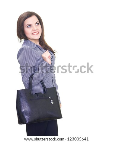 Attractive smiling young woman in a gray blouse, holding a black handbag. Isolated on white background