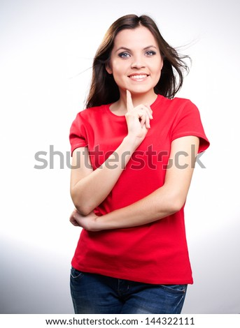 Attractive smiling young woman in a red shirt holding her finger on her chin. on white background