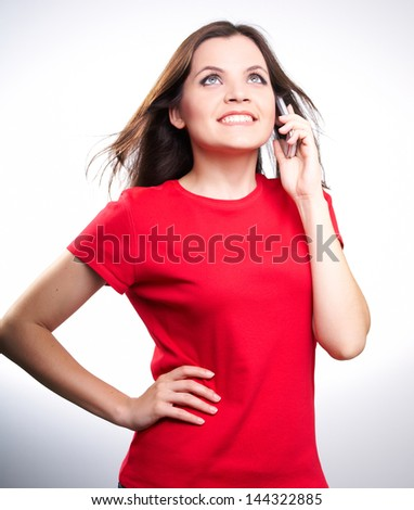 Attractive smiling young woman in a red shirt talking on a mobile phone,on white background
