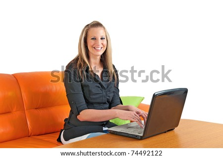 Attractive smiling young woman sitting at home using a laptop - stock photo
