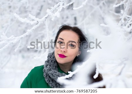Attractive smiling young women stays in the winter park. Bright lips. Snow covered branches ahead. Winter season.