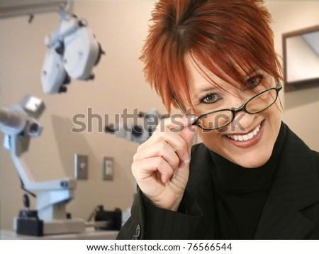 Attractive 30 something red head eye doctor in exam room.  Smiling, wearing eyeglasses. Ophthalmology Ophthalmologist - stock photo