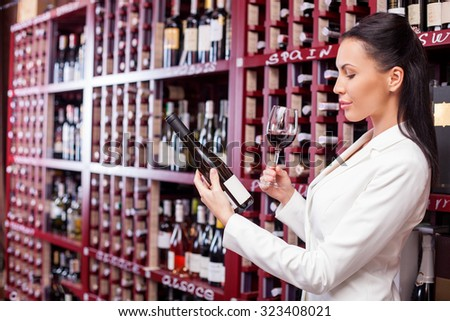 Attractive sommelier is drinking red wine with enjoyment. The woman is holding a wineglass and holding a bottle of wine. She is looking at it confidently and smiling. She is standing in cellar - stock photo